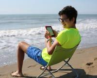El muchacho caucásico sonriente lee un ebook que se sienta en la silla de playa Fotos de archivo libres de regalías