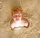 El muchacho cavaró en la arena de la playa Foto de archivo libre de regalías