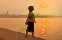 El muchacho cerca del río mira una puesta del sol hermosa Imágenes de archivo libres de regalías