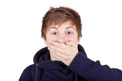El muchacho cerró su boca con una mano Fotos de archivo libres de regalías