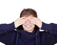 El muchacho cerró sus ojos con las manos Foto de archivo libre de regalías