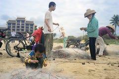 El muchacho chino ayuda a padres a desenredar una red de pesca fotografía de archivo