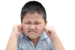 El muchacho cierra los oídos con los fingeres para proteger contra fuerte ruido foto de archivo libre de regalías