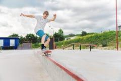 El muchacho coge el equilibrio en el manual y el resbalón Foto de archivo