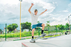 El muchacho coge el equilibrio en el manual y el resbalón Fotos de archivo libres de regalías