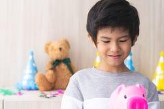 El muchacho coge la hucha para el presente de cumpleaños foto de archivo