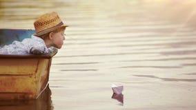 El muchacho coloca un barco de papel en la superficie del agua y sopla para que navegue lejos almacen de metraje de vídeo