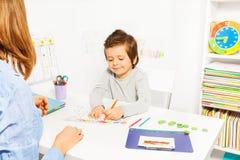 El muchacho colorea formas durante el ABA con el terapeuta cerca Fotografía de archivo