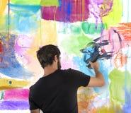 El muchacho colorea una pared Imagenes de archivo