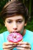 El muchacho come el buñuelo con la fresa rosada Fotografía de archivo