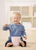 El muchacho come el helado de la tina Fotos de archivo libres de regalías