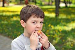 El muchacho come el huevo de chocolate con una sorpresa Foto de archivo
