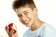 El muchacho come la manzana Imagen de archivo libre de regalías