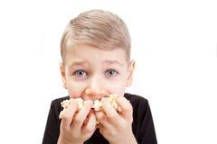 El muchacho come las palomitas Imagen de archivo