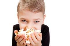 El muchacho come las palomitas Fotos de archivo libres de regalías