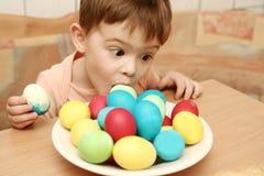 El muchacho come los huevos de Pascua Fotos de archivo