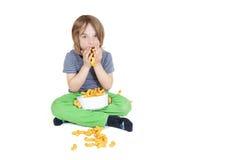 El muchacho come microprocesadores del cacahuete Fotografía de archivo