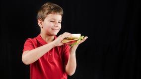 El muchacho come un bocadillo, que aparece mágico en sus manos, s almacen de video