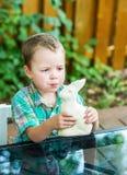El muchacho come un conejito blanco del chocolate Foto de archivo