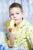 El muchacho come un plátano Imágenes de archivo libres de regalías