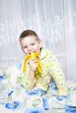 El muchacho come un plátano Foto de archivo libre de regalías