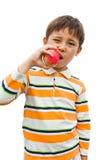 El muchacho come una manzana buena para la salud Fotografía de archivo libre de regalías