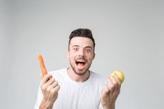 El muchacho come una zanahoria y una manzana Imágenes de archivo libres de regalías