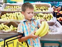 El muchacho compra plátanos en tienda Fotos de archivo libres de regalías