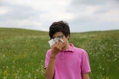 El muchacho con alergia y la camiseta rosada sopla su nariz usando un handker Imagenes de archivo