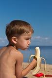 El muchacho con apetito come el plátano imagenes de archivo