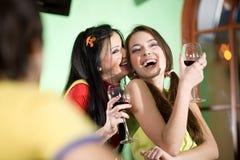 El muchacho con dos muchachas está bebiendo el vino Imágenes de archivo libres de regalías