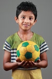 El muchacho con el cuerpo manchado con fango lleva a cabo un fútbol Foto de archivo