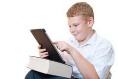 El muchacho con el ordenador del libro y de la tablilla Imagenes de archivo