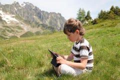 El muchacho con el panel táctil se sienta en cuesta en las montañas Imágenes de archivo libres de regalías