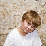 El muchacho con el pelo marrón claro y el marrón observa los lookes amistosos Foto de archivo libre de regalías