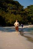 El muchacho con el pelo rojo en el baño de los paños está caminando en un hermoso sea Imágenes de archivo libres de regalías