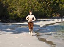 El muchacho con el pelo rojo en el baño de los paños está caminando en un hermoso sea Foto de archivo