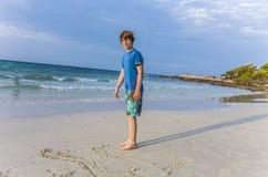 El muchacho con el pelo rojo está escribiendo un mensaje en la playa arenosa Imagenes de archivo
