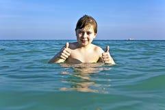 El muchacho con el pelo rojo está gozando del agua caliente clara en el beauti foto de archivo libre de regalías