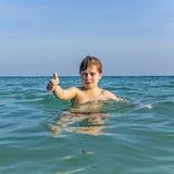 El muchacho con el pelo rojo está gozando del océano Fotos de archivo