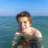 El muchacho con el pelo rojo está gozando del océano Foto de archivo libre de regalías
