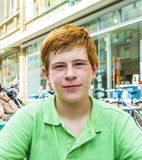 El muchacho con el pelo rojo está pareciendo feliz y amistoso Foto de archivo libre de regalías