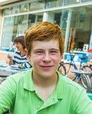 El muchacho con el pelo rojo está pareciendo feliz y amistoso Imagen de archivo libre de regalías