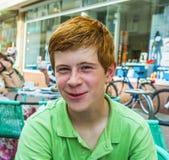 El muchacho con el pelo rojo está pareciendo feliz y amistoso Imagenes de archivo