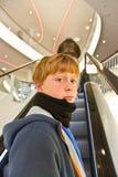 El muchacho con el pelo rubio se está colocando en una escalera móvil Fotografía de archivo