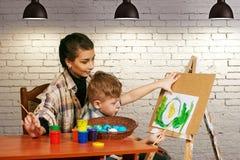 El muchacho con el profesor en la pintura La capacidad de dibujar Foto de archivo
