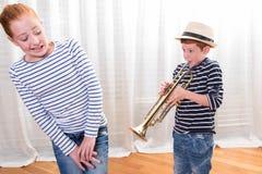 El muchacho con el sombrero está tocando la trompeta - hermana enfadada Fotos de archivo