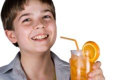 El muchacho con el zumo de naranja fotografía de archivo