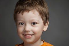 El muchacho con emociones positivas en un fondo gris, niño sonríe ch Imagen de archivo
