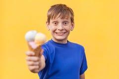 El muchacho con helado en fondo amarillo Fotografía de archivo libre de regalías